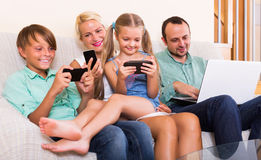 Family working with smartphones. Smiling young mom, dad and two kids working with smartphones indoors Stock Photos