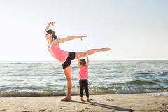 Family workout - mother and daughter doing exercises on beach. Mom and child working out on seaside in the morning. Healthy lifestyle concept Stock Photography