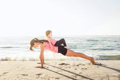 Family workout - mother and daughter doing exercises on beach. Mom and child working out on seaside in the morning. Healthy lifestyle concept Stock Image