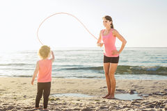 Family workout - mother and daughter doing exercises on beach. Mom and child working out on seaside in the morning. Healthy lifestyle concept Royalty Free Stock Images
