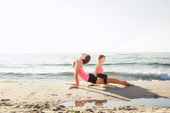 Family workout - mother and daughter doing exercises on beach. Mom and child working out on seaside in the morning. Healthy lifestyle concept Stock Photos