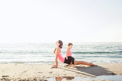 Family workout - mother and daughter doing exercises on beach. Mom and child working out on seaside in the morning. Healthy lifestyle concept Royalty Free Stock Photography