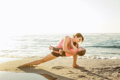 Family workout - mother and daughter doing exercises on beach. Royalty Free Stock Photos