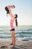 Family workout - mother and daughter doing exercises on beach. Stock Images