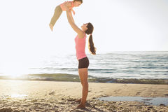 Family workout - mother and daughter doing exercises on beach. Royalty Free Stock Image