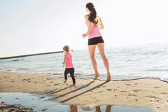 Family workout - mother and daughter doing exercises on beach. Stock Photography