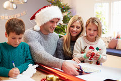 Family Wrapping Christmas Gifts At Home Royalty Free Stock Image