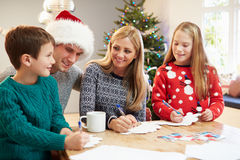 Family Writing Christmas Cards Together Stock Image