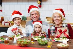 Family with xmas presents. Senior couple and their grandchildren in Santa caps holding their xmas presents while sitting by festive table Royalty Free Stock Photo