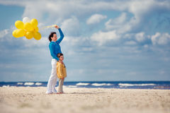 Family with yellow balloons on the beach Stock Photo