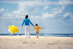 Family with yellow balloons on the beach Royalty Free Stock Image