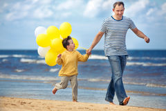 Family with yellow balloons playing on the beach Stock Images