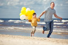 Family with yellow balloons playing on the beach Royalty Free Stock Photo