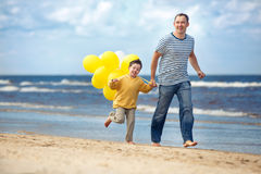 Family with yellow balloons playing on the beach Stock Photography