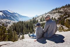 Family in yosemite. Family of two, father and son, sitting and enjoying the view at beautiful mountains at tioga pass in yosemite national park, active vacation Stock Photography