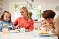 Family With Young Baby Eating Meal At Home Royalty Free Stock Image