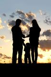 Family with Young Child Silhouette at Sunset Royalty Free Stock Image
