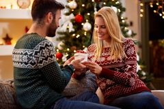 Family couple surprising each other with Christmas presents Royalty Free Stock Image