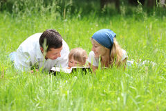 Family with a young daughter reads the Bible Stock Photo
