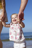 Family With Young Daughter Walking Along Beach Together Royalty Free Stock Images