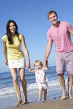 Family With Young Daughter Walking Along Beach Together Royalty Free Stock Image