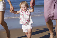 Family With Young Daughter Walking Along Beach Together Stock Images