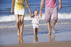 Family With Young Daughter Walking Along Beach Together Royalty Free Stock Photography