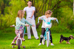 Family of young father and little kids biking at. Family of father and kids biking at summer vacation Stock Photos