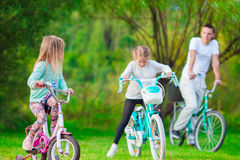 Family of young father and little kids biking at summer warm day. Happy family biking at summer warm day Stock Photography