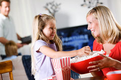 Family: Young Giirl Takes Popcorn From Bowl Stock Photos