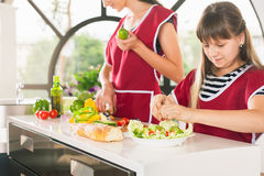 Family of young girls cooking. Recipe healthy food for kids Royalty Free Stock Photography