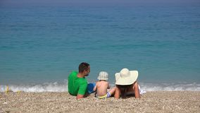 Family, young parents and little child resting on beach, turquoise sea waving. UHD 4K stock video