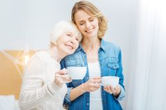 Cute young woman closing her eyes and smiling while being with grandmother. Family. Young pretty cheerful women closing her eyes and smiling while leaning her Royalty Free Stock Photography