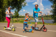 Family with young son riding on scooter Royalty Free Stock Photography