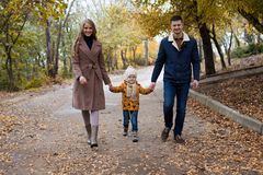 A family with a young son walk in the Park in autumn royalty free stock photos