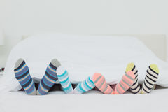 Familys feet in stripey socks. At home in bed royalty free stock photos