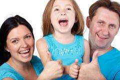 Familyshouts och ger upp deras tum. Royaltyfria Bilder