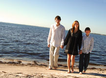 Famiy at beach. A happy smiling group of three youth walking by the beach stock photo