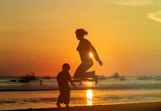 Famiy jumping at sunset Stock Photos