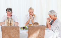 Família bonita que praying na tabela Imagens de Stock Royalty Free