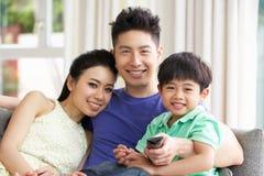 Família chinesa que presta atenção à tevê no sofá junto Fotografia de Stock Royalty Free