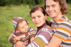 A família com o bebê na listra veste-se no parque Fotografia de Stock