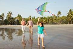 Família da raça misturada que tem o resto na praia Foto de Stock