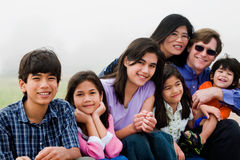 Família de sete multirracial que sentam-se na praia Fotos de Stock Royalty Free