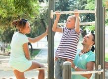 A família de três que treina junto sobre levanta a barra Foto de Stock Royalty Free