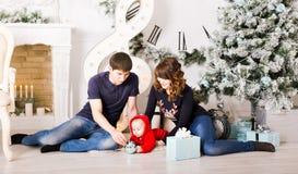 Família do Natal com os presentes da abertura do bebê feliz Fotografia de Stock