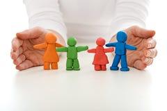 Família dos povos da argila protegida pelas mãos da mulher Imagem de Stock Royalty Free