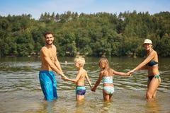 Família e duas crianças em um lago Imagem de Stock