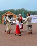 A família em vestidos nacionais fino-úgricos dança em um círculo Foto de Stock