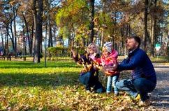 Família europeia despreocupada que joga no parque outonal Foto de Stock Royalty Free